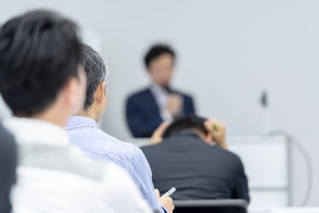 会議で頭を抱える男性。