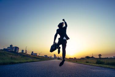 朝日に向かってジャンプするビジネスマン