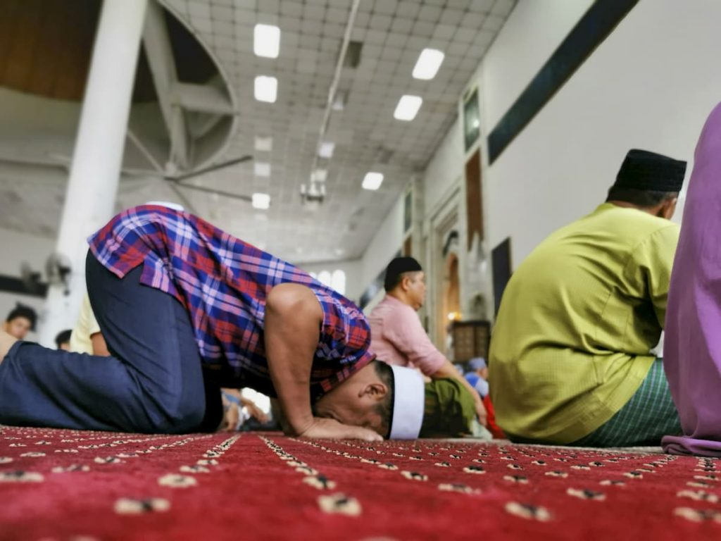 男性がモスクでお祈りをしている