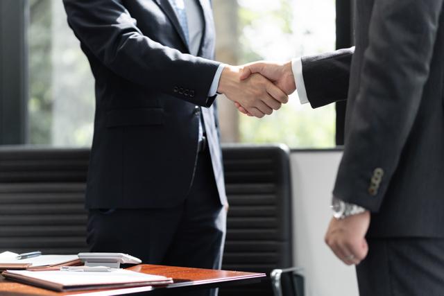 営業先の担当と握手するビジネスマン。