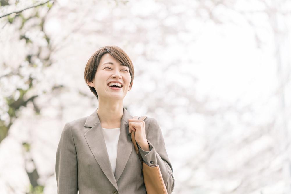 桜を背にして笑う女性。